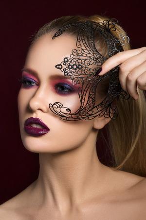 maquillaje de fantasia: Close-up retrato de la belleza de la mujer bastante joven rubia con la noche de maquillaje la celebración de la máscara del partido negro en la mano.