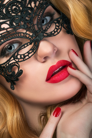 masquerade mask: Close-up portrait of young sensual ginger woman wearing black party mask