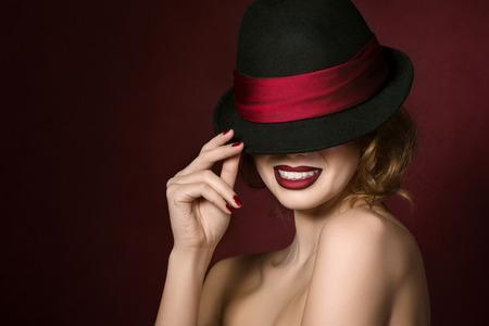 mujeres elegantes: Retrato de joven bella actriz sostiene el sombrero negro con cinta roja sobre fondo rojo oscuro