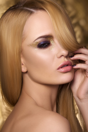 pink lips: Portrait of young sensual woman touching her face over golden background