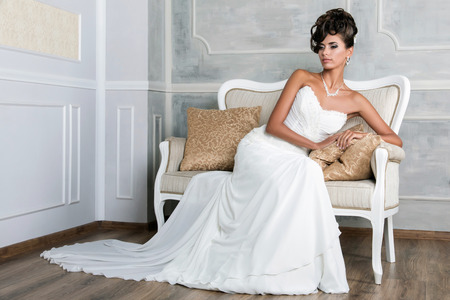 Portrait of young luxurious brunette bride sitting on vintage sofa in beautiful wedding dress photo