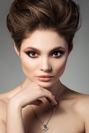 Close-up portret van jonge mooie brunette vrouw aan te raken haar gezicht met hartvormige kristallen hanger Stockfoto