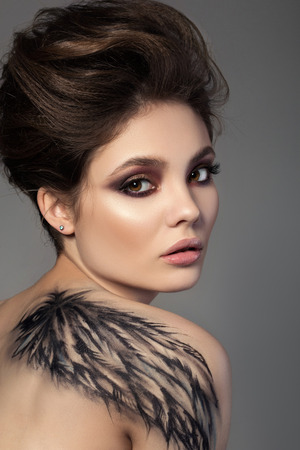 hair feathers: Portrait of young sensual brunette woman with black wing bodyart on her back