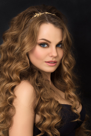 Portrait of gorgeous young woman with long curly hair over dark background photo