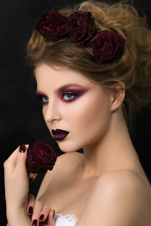 dark eyes: Close-up portrait of young woman with dark violet party make-up holding dark red withered rose