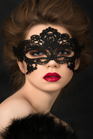 mysterious: Portrait of young adorable woman wearing black party mask Stock Photo