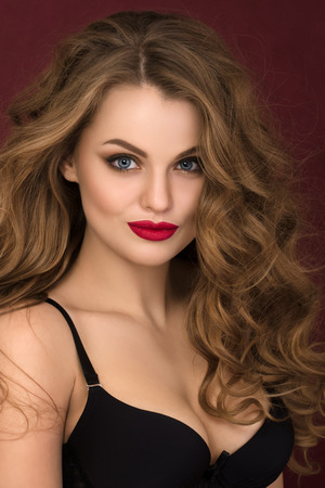 red bra: Portrait of coquette young curly woman with red lips  looking straight to camera