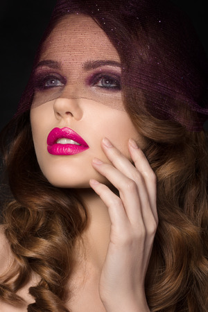 Portrait of young beautiful aristocratic woman with bright pink lips wearing purple veil and touching her face photo