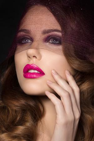 mujeres elegantes: Retrato de joven bella mujer con rizos marrones y rosados ??labios brillantes que miran a trav�s del velo p�rpura