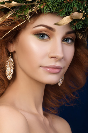 firry: Portrait of young beautiful redhaired woman with firry wreath with golden leaves in her hair. SPA or skincare concept.