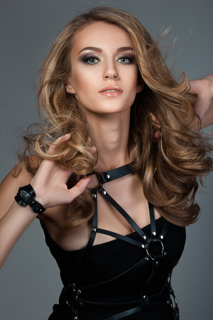 glam rock: Portrait of young beautiful woman with flying-away hair wearing black dress with leather bands