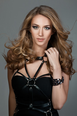 Portrait of young beautiful woman with flying-away hair wearing black dress with leather bands photo