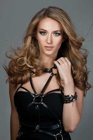 capelli lunghi: Ritratto di giovane donna bellissima con i capelli battenti a scomparsa che indossa un abito nero con fasce in pelle Archivio Fotografico