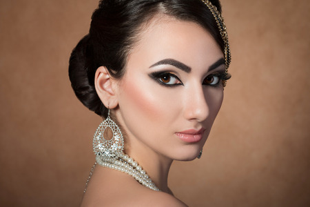 silver jewellery: Portrait of young beautiful asian woman with evening make-up over beige background