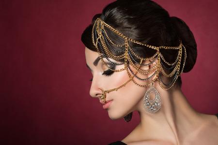 fille indienne: Portrait de la belle jeune femme asiatique avec maquillage de soirée de porter des accessoires de tête sur fond rouge foncé