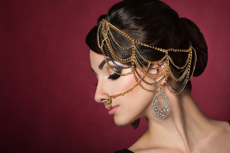 asian girl face: Portrait of young beautiful asian woman with evening make-up wearing head accessories over dark red background Stock Photo