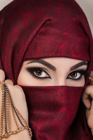 hijab: Portrait of beautiful arabian girl hiding her face behind red niqab with paisley ornament