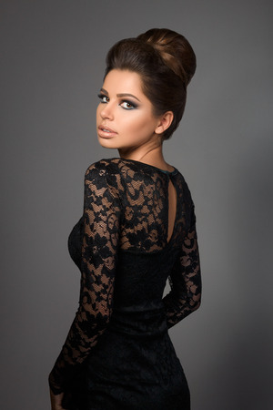Beautiful young model in black dress with evening makeup and hairdo standing back to camera and looking back over her shoulder