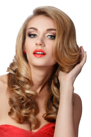 coiffure: Portrait of beautiful woman in red dress doing up her hair. Wedding coiffure and make-up.