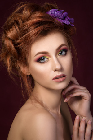 redhaired: Portrait of beautiful red-haired woman with purple hair-slide looking straight to camera and touching her face Stock Photo