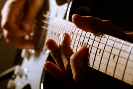 Hands of man playing electric guitar. Low key photo.