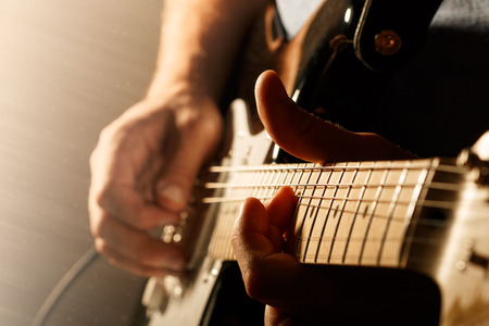 man playing guitar: Hands of man playing electric guitar. Bend technique. Low key photo.