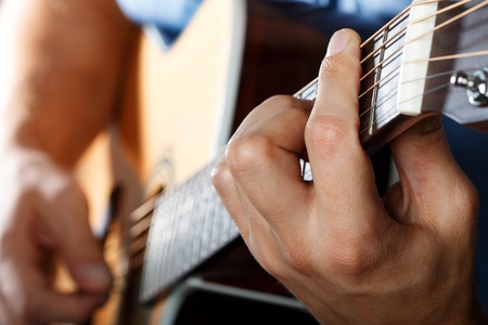barre: Acoustic guitar player performing song. Hands closeup
