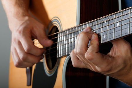 music player: Acoustic guitar player performing song. Hands closeup