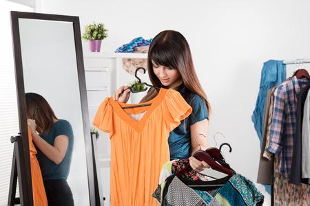 ropa casual: Mujer joven hermosa cerca de rack con la toma de ropa chioce
