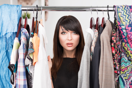 woman closet: Portrait of young confused woman in front of a wardrobe full of clothes. Nothing to wear concept