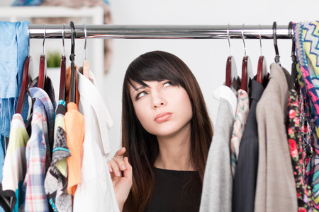 Beautiful young confused woman near rack with clothes. Nothing to wear concept Standard-Bild