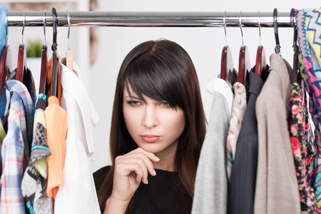 clothes rack: Beautiful young confused woman near rack with clothes. Nothing to wear concept Stock Photo