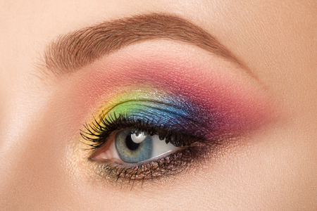 multicolored eye macro: Close-up view of blue female eye with beautiful modern creative make-up