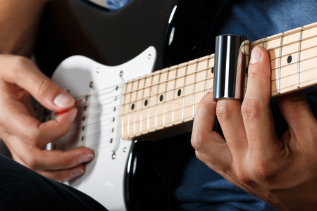 performing: Electric guitar player performing song with slider