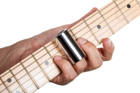 fretboard: Hands of man playing electric guitar. Guitarist hands. Fingers with metallic slider pressing strings on maple fretboard closeup