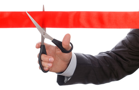 cut wrist: Hand of businessman in suit cutting red ribbon with pair of scissors isolated on white background. Grand opening concept. Traditional public festive ceremony.
