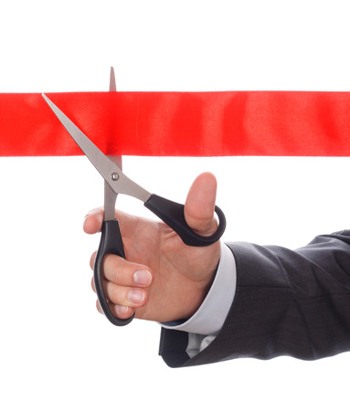 ribbon cutting: Hand of businessman in suit cutting red ribbon with pair of scissors isolated on white background. Grand opening concept. Traditional public festive ceremony.