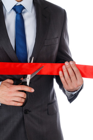unveiling: Businessman in suit cutting red ribbon with pair of scissors isolated on white background. Grand opening concept. Traditional public festive ceremony. Stock Photo