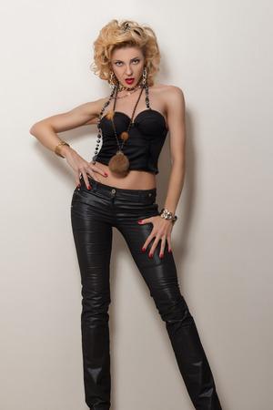labios sensuales: Mujer adulta rubia atractiva en corsé negro y un pantalón que presenta sobre el fondo blanco Foto de archivo