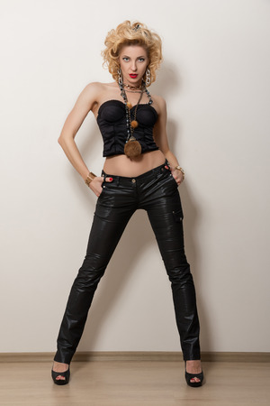 female sexy chains: Sexy blond adult woman in black corset and trousers posing over white background