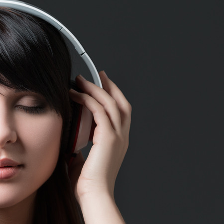 earbuds: Close-up portrait of young beautiful brunette woman listening to music and holding white headphones