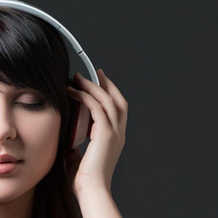 listening to music: Close-up retrato de la joven y bella mujer morena escuchar m�sica y la celebraci�n de los auriculares blancos