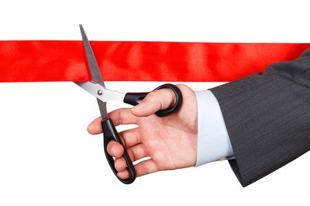 tijeras: Hombre de negocios en traje de corte de cinta roja con un par de tijeras aisladas sobre fondo blanco. Concepto inauguraci�n. Ceremonia festiva p�blico tradicional. Foto de archivo