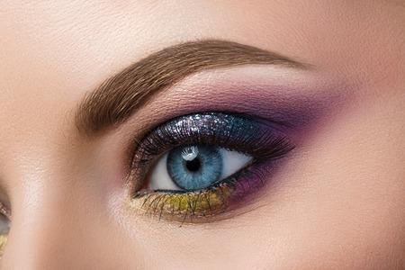 ojos hermosos: Vista de primer plano de mujer de ojos azul con hermosas moderno maquillaje creativo
