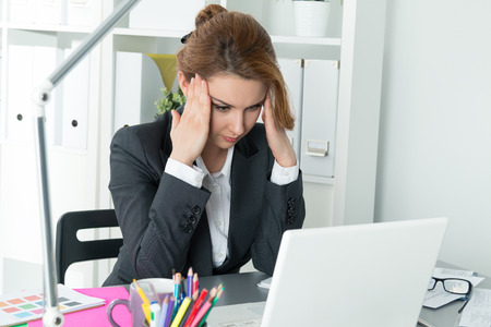 empleados trabajando: Joven mujer de negocios hermosa tratando de concentrarse mira el monitor del ordenador port�til Foto de archivo