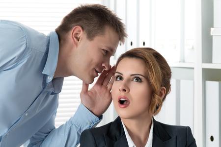 chismes: Hombre joven que dice chismes a su colega de la mujer en la oficina. Intrigas y perder concepto de tiempo Foto de archivo