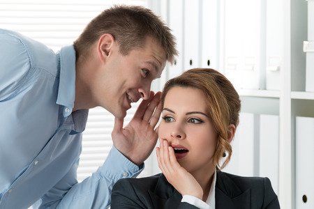 plot: Young man telling gossips to his woman colleague at the office. Intrigues and wasting time concept