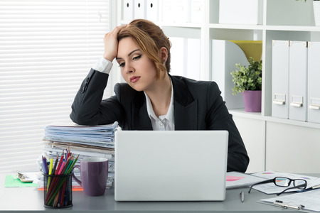 stressed business woman: Tired stressed business woman sitting with huge pile of papers
