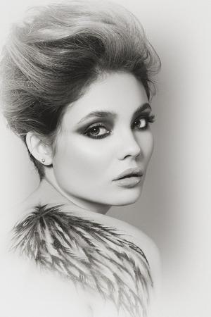 tatouage ange: Portrait en noir et blanc d'une jeune femme sensuelle en noir art corporel de l'aile sur le dos