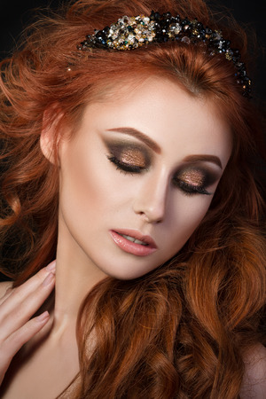 redhaired: Portrait of beautiful sensual red-haired woman with black hair accessory looking down and touching her neck Stock Photo
